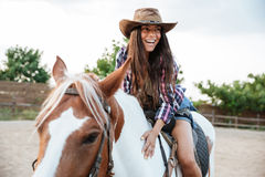 Smiling cute young womna cowgirl riding a horse outdoors Stock Image