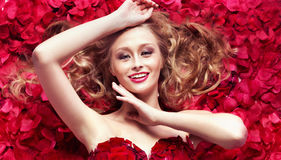 Smiling cutie among rose petals. Smiling cutie among red rose petals stock photo