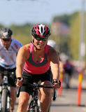 Smiling, cycling woman wearing pink tank-top. STOCKHOLM - AUG 23, 2015: Smiling, cycling woman wearing pink tank-top followed by de-focused competitors at ITU Royalty Free Stock Photos