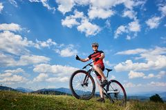 Smiling cyclist in sportswear and helmet standing with cross country bike on top of hill stock photography