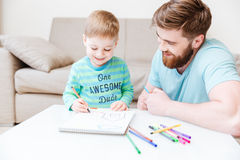 Smiling dad and little son drawing with colorful markers Stock Photo