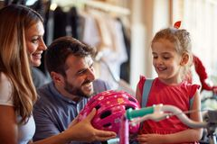 Smiling dad and mom buying new bicycle for little girl in bike shop. Smiling dad and mom buying new bicycle for happy little girl in bike shop stock photo
