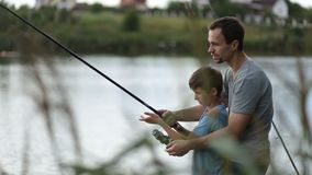 Smiling dad and son fishing and relaxing at pond stock video