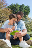 Smiling dad and son inspecting leaf with a magnifying glass. In the park Royalty Free Stock Photos