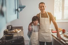 Smiling dad and son posing in aprons. Portrait of father and kid making pastry in kitchen. They standing in embrace and looking at camera with satisfaction Royalty Free Stock Photography