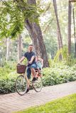 Smiling Dad and son riding bicycles outdoors in a city park royalty free stock photo