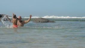 Daddy plays with cute son splashing water in azure ocean bay