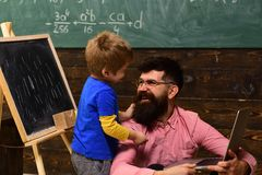 Smiling daddy teaching his son new skills. Father and son looking at each other with love. Standing kid hugging his. Sitting dad. Home education concept Royalty Free Stock Photo