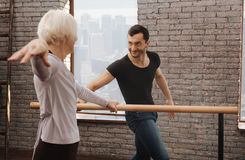 Smiling dance instructor teaching pensioner in the dance studio. Working diligent for success. Positive charming experienced dancer teaching elderly women while Royalty Free Stock Image