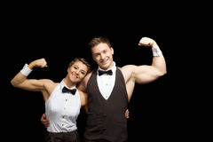 Smiling dancers shows biceps,  on black Stock Photography