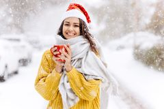Smiling dark-haired girl in a yellow sweater, a white scarf in Santa Claus hat is standing with a red mug on a snowy royalty free stock photography