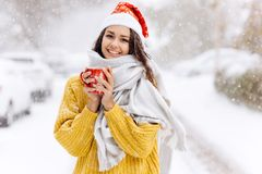 Smiling dark-haired girl in a yellow sweater, a white scarf in Santa Claus hat is standing with a red mug on a snowy. Street on a winter day royalty free stock photos