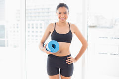 Smiling dark haired model in sportswear carrying a blue exercise mat Royalty Free Stock Image