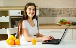 Woman Chats Happily on Laptop. Smiling dark-haired woman chatting on the laptop, having juice during the chat, positive relaxing atmosphere at sweet home stock photos