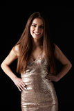 Smiling dark haired woman in evening dress, hands on hips Royalty Free Stock Photography