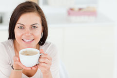 Smiling dark-haired woman having a coffee Royalty Free Stock Images