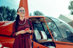 Smiling dark-haired woman in red outfit waiting for the pilot. Helicopter on the back. Smiling dark-haired woman in red outfit waiting for the pilot while royalty free stock images