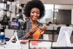 Smiling dark-skinned woman in an orange top looking amused. Fashion look. Smiling dark-skinned woman wearing an orange top looking amused while demonstrating a royalty free stock photos