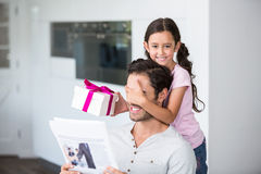 Smiling daughter covering father eyes while holding gift box Royalty Free Stock Photo