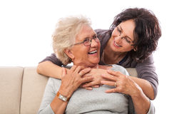 Smiling daughter embracing old mother Royalty Free Stock Photography