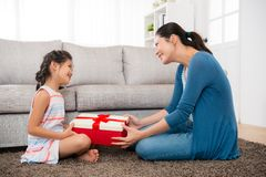 Smiling daughter gave her mother a red gift box. In mother`s day festival holiday and sitting together in front of the living room sofa on the floor happiness Royalty Free Stock Photos