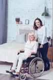 Smiling daughter helping disabled mother at home. Full of delight. Cute cheerful young daughter standing in the bedroom and taking care of old disabled mother Stock Image