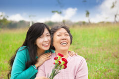 Smiling daughter and her mother. Asian Smiling daughter and her mother with carnation flower on the grass field Royalty Free Stock Images