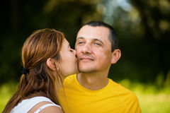 Smiling daughter kissing her mature father Royalty Free Stock Image