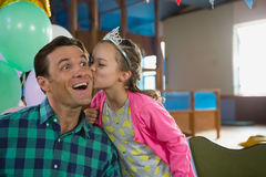Smiling daughter kissing his father. At home Stock Images