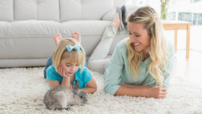 Smiling daughter and mother laying on the floor with rabbit Stock Photos