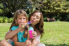 Smiling daughter with mother making bubbles Royalty Free Stock Photos