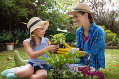 Smiling daughter and mother with potted plants. Sitting on grass in backyard Royalty Free Stock Photos