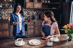 Daughter spreading toast with chocolate paste. Smiling daughter spreading toast with chocolate paste and looking on mother in the kitchen Stock Photography