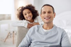 Smiling daughter standing behind her father. My precious. Handsome exuberant dark-haired father sitting in the arm-chair and smiling and his daughter standing Royalty Free Stock Photography