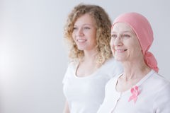 Supporting mother battling breast cancer. Smiling daughter supporting mother battling breast cancer wearing pink headscarf Royalty Free Stock Photography