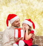 Smiling daughter waiting for present from father Stock Photo
