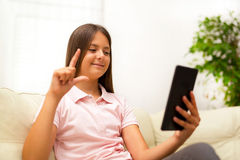Smiling deaf girl talking using sign language on digital tablet. At home stock photography