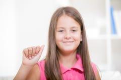 Smiling deaf girl using sign language. Beautiful smiling deaf girl using sign language, isolated on white stock image