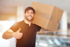 Smiling delivery man with box. In business center stock photo