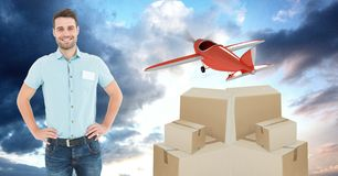 Smiling delivery man with boxes and plane flying in background Royalty Free Stock Photo