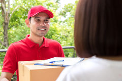 Smiling delivery man delivering parcel to a woman Stock Photos