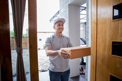 Delivery man delivering box. Smiling delivery man in grey uniform delivering parcel box to recipient Royalty Free Stock Photos