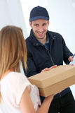 Smiling delivery man handing package to woman Stock Images
