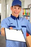 Smiling delivery man, holding clip board and carton box. Inside office Stock Image