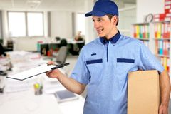 Smiling delivery man, holding clip board and carton box. Inside office Stock Photo