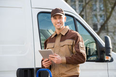 Smiling Delivery Man Holding Digital Tablet Against Truck Royalty Free Stock Images