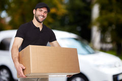 Smiling delivery man. Holding a paper box Royalty Free Stock Images