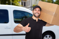 Smiling delivery man. Holding a paper box Stock Photos