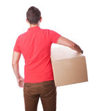 Smiling delivery man is holding a paper box. Back view. Stock Image