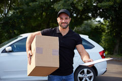 Smiling delivery man. Holding a paper box and folder Stock Photo